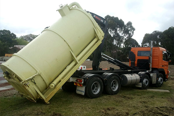 10,000 litre tank being unloaded off the hook truck into position next to jacking pit